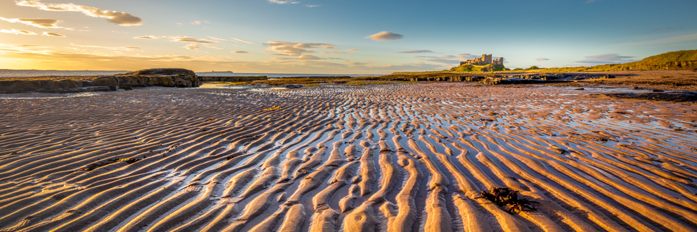 Bamburgh Castle on a summer morning with ripples sand